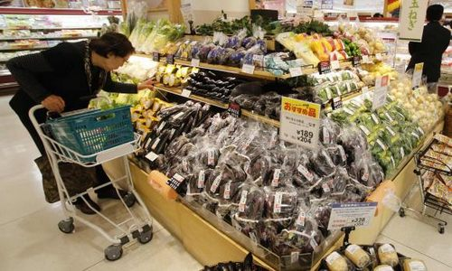 A shopper looks at vegetables at an Ito-Yokado shopping centre after a sales tax hike in Tokyo